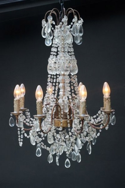 Ornate Candle Chandelier on dark wall background with lights on lifestyle image