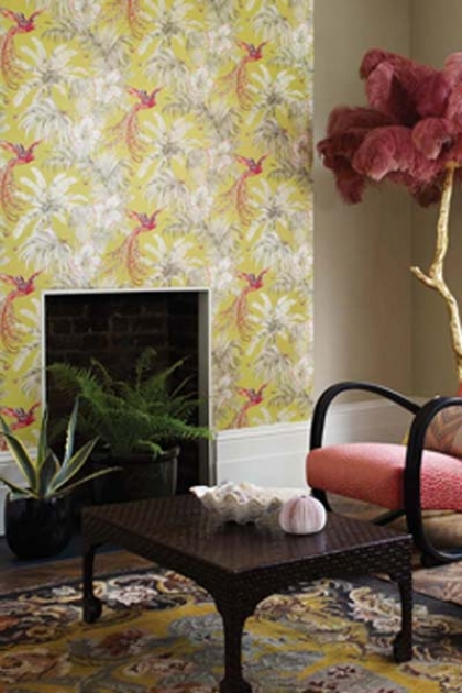 lifestyle image of Matthew Williamson Birds of Paradise Wallpaper - 4 Colours Available with black fireplace and dark wooden coffee table with pink velvet chair and large pink feather and gold tree ornament