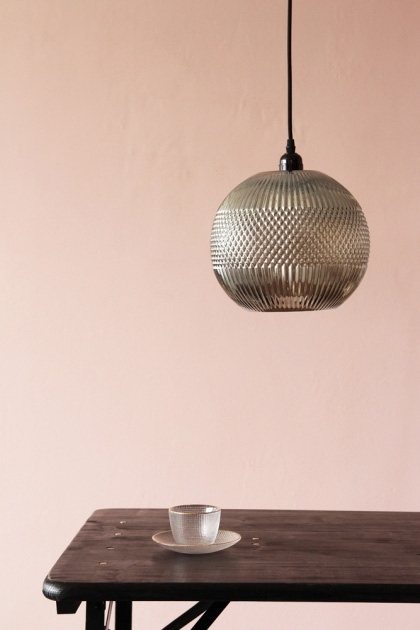 lifestyle image of Pacific Glass Pendant Light over wooden table with glass tea cup and saucer and pink wall background