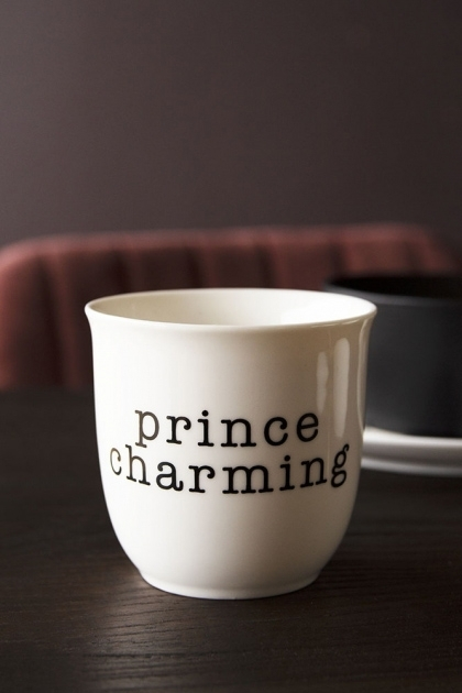 Lifestyle image of the Prince Charming Bone China Mug on black table with tableware and red velvet dining chair in background with dark wall