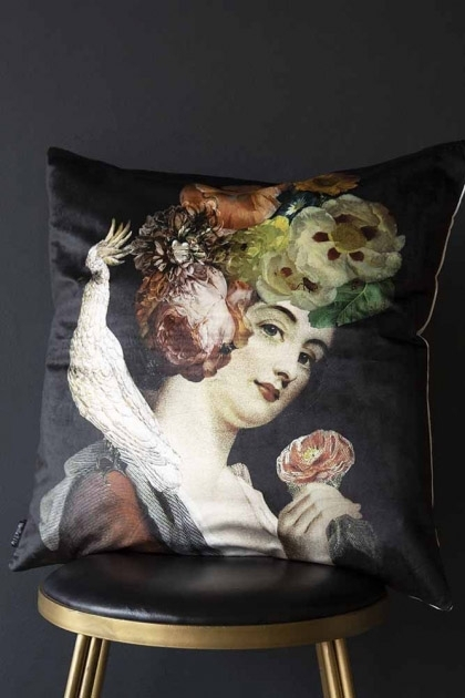 lifestyle image of the Quirky lady with floral headdress and cockatoo black velvet cushion sat on a stool with dark grey background