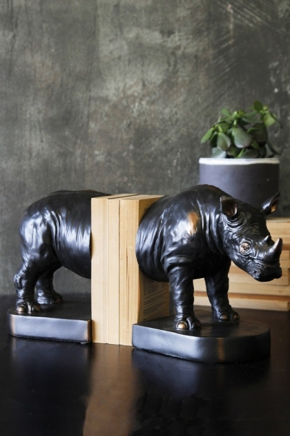 lifestyle image of Rhino Bookends with books in between and plant on black table and distressed wall background