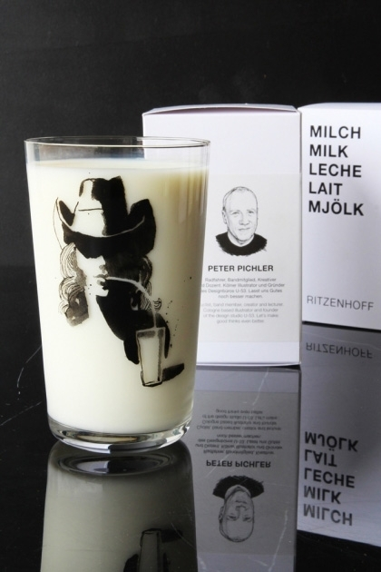 lifestyle image of Ritzenhoff Milk Glass - Peter Pichler with black cowboy on and milk in and box in background on black table