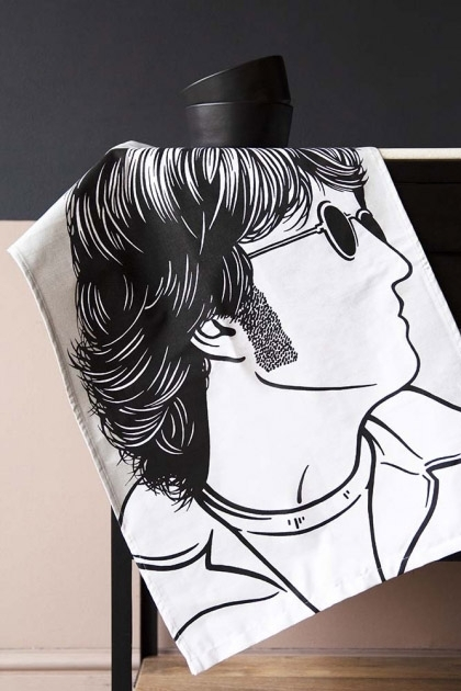 Lifestyle image showing the John Lennon T-Towel hanging from a table with a black plant pot and contrasting wall colours background