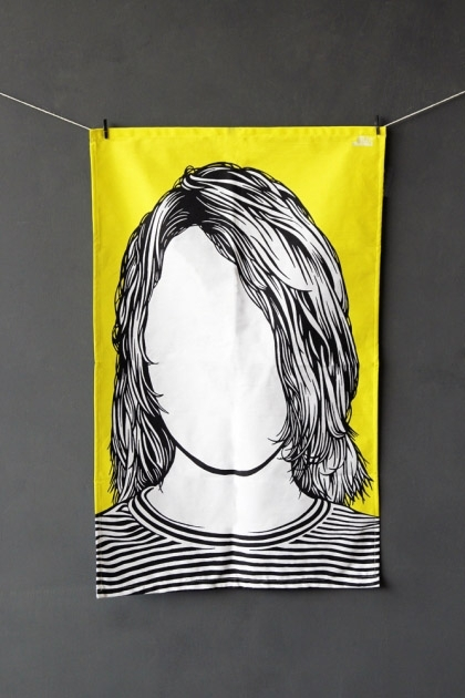 lifestyle image of Rock Icon Tea Towel - Kurt Cobain black and white with yellow background pegged on string with dark grey wall background