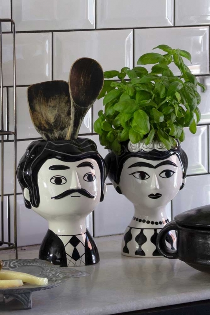 Lifestyle image of both Marisol and Carlos, the Mexican vases with wooden spoons and plants on white and black tiled background and marble effect surface