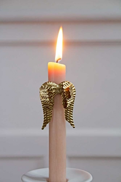 Image of the Gold Angel Wings Candle Ornament on a lit candle