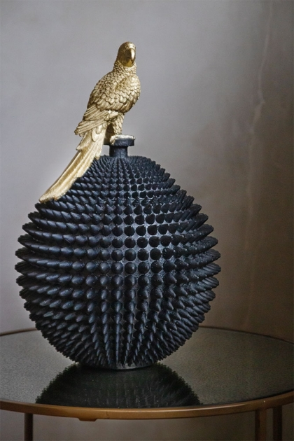 Lifestyle image of the Black Spiked Ball Storage Jar With Gold Parrot
