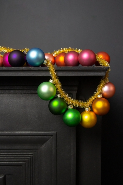 Image of the Large Rainbow Baubles & Tinsel Garland draped on a fireplace