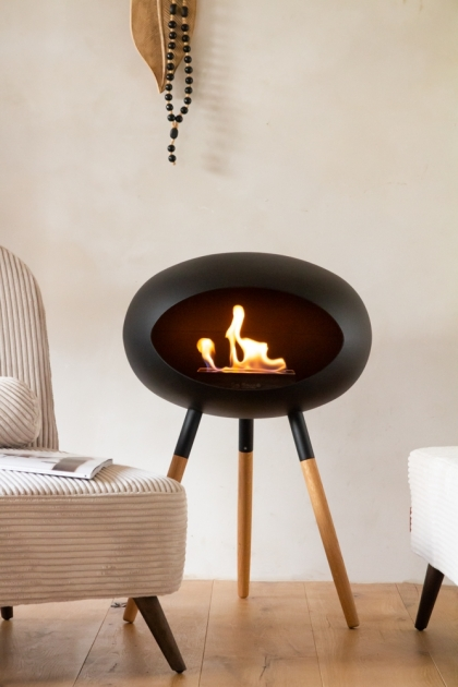 Lifestyle image of the Low Le Feu Ground Wood Eco Fireplace in Oak & Black