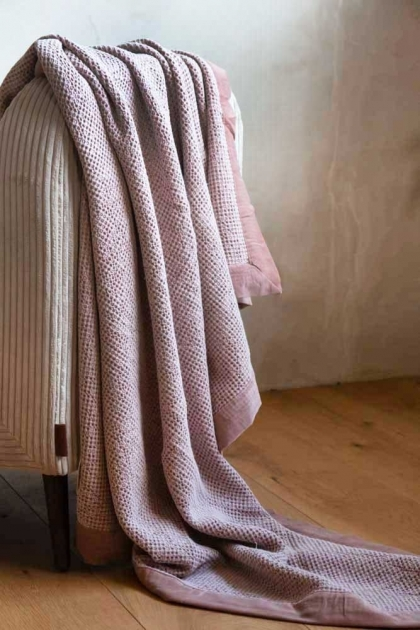 Lifestyle image of the Luxurious Waffle Throw with Velvet Edging In Dusky Pink