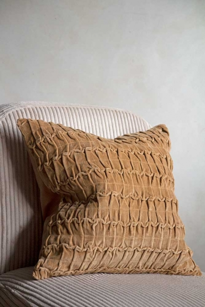Lifestyle image of the Camel Ruched Velvet Cushion on a chair