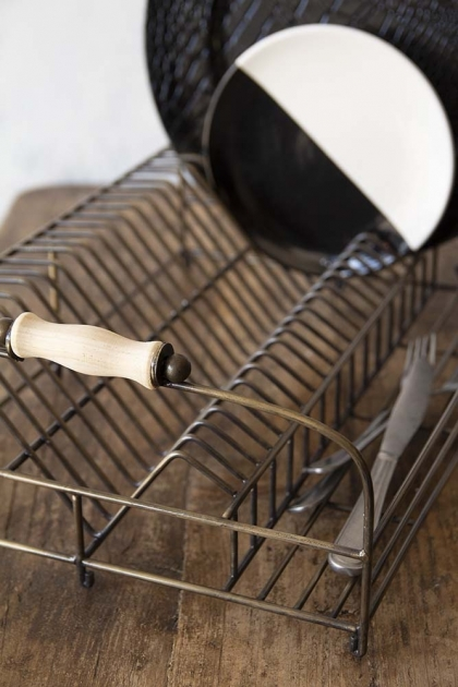 Lifestyle image of the Antique Brass Finish Wire Dish Rack with black and white dishes inside on wooden surface