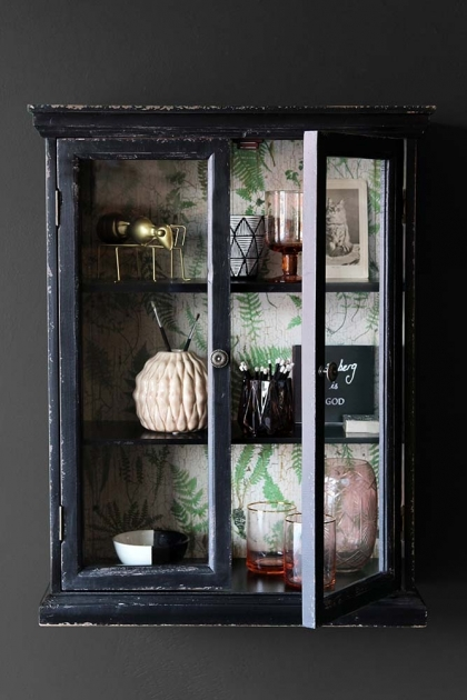 Distressed black cabinet on a dark wall with ornaments and pictures on the three shelves inside it - Rockett St George