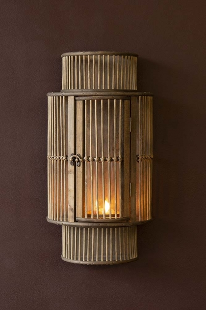 Lifestyle image of the Bamboo Curved Wall Lantern with a candle lit inside it