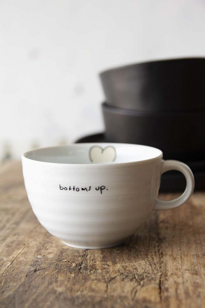 Lifestyle image of the Bottoms Up Cappuccino Coffee Cup on wooden table and white wall with black bowls in background