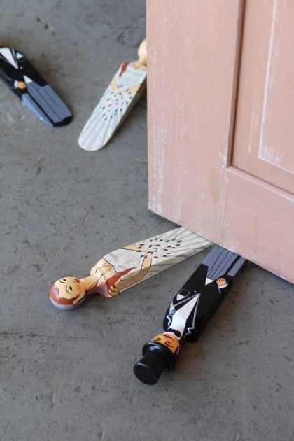Lifestyle image of the Bride & Groom Doorstops under a pink door on a grey concrete floor