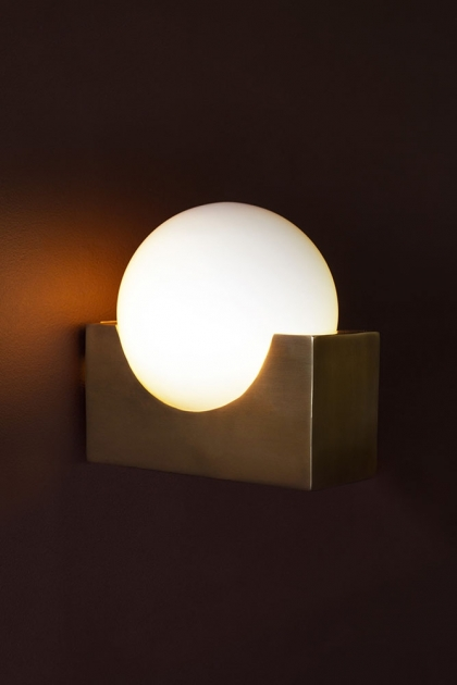 Lifestyle image of the Atlas Globe Wall Light on a wall switched on on dark wall background