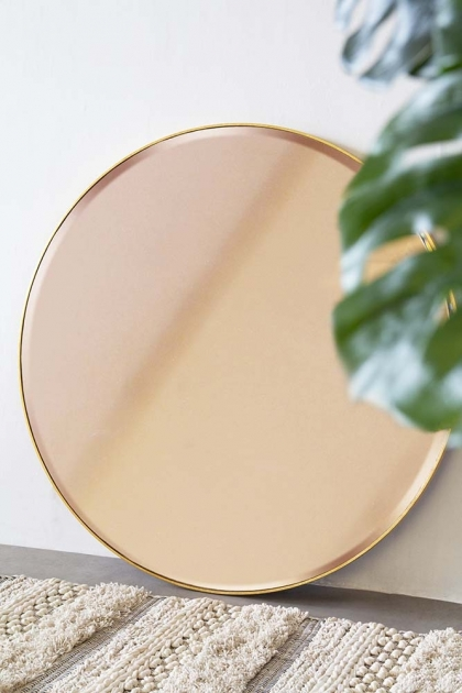 Lifestyle of round rose gold mirror leaning on the floor