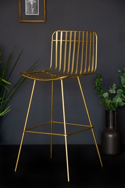 Side angle lifestyle image of the Midas Bar Stool with plants and black flooring and copper picture frame on dark wall background