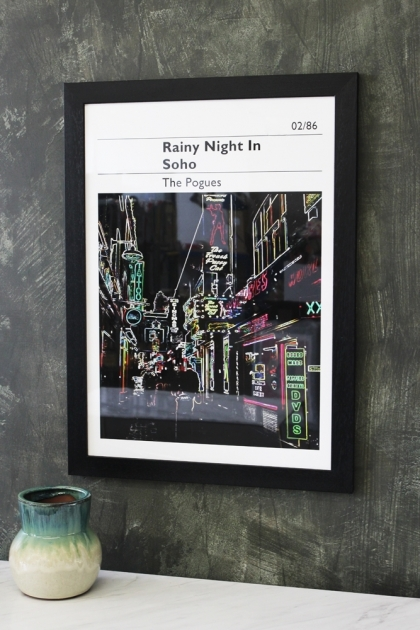 lifestyle image of Unframed Rainy Night In Soho - The Pogues Art Print in black frame above white table with blue vase and distressed wall background