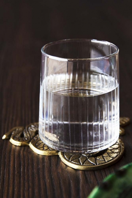 Lifestyle image of the Elegant Engraved Stripes Tumbler Water Glass on a coaster with water in it