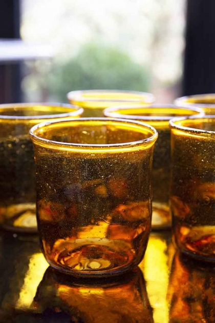 Close-up lifestyle shot of the amber set of 6 recycled glass water tumblers