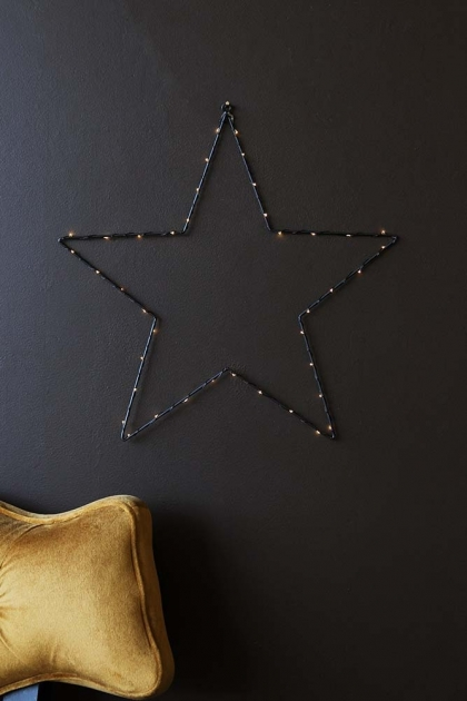 lifestyle image of Star Light Decoration - Battery Operated with golden ochre velvet cloud chair on dark wall background