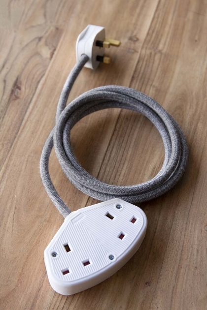 lifestyle Image of the Stylish 2m Extension Cable - Grey Linen Lead With White Sockets on a pale wooden floor background