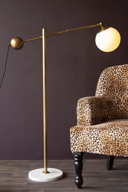 Lifestyle image of the Atlas Globe Angled Floor Lamp With Marble Base switched on