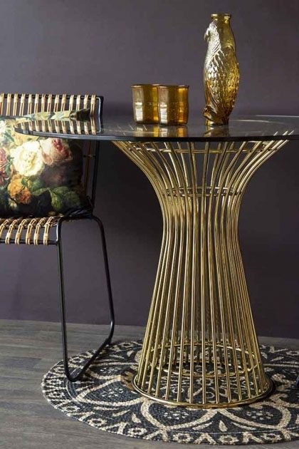 Lifestyle image of the Round Glass Top Dining Table with glasses on top with dark wall background and rug on floor