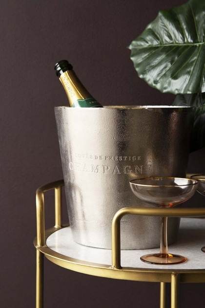 Lifestyle image of the Rustic Cuvee De Prestige Champagne / Wine Cooler with bottle inside on marble and gold drinks trolley with champagne glass and house plant on dark wall background