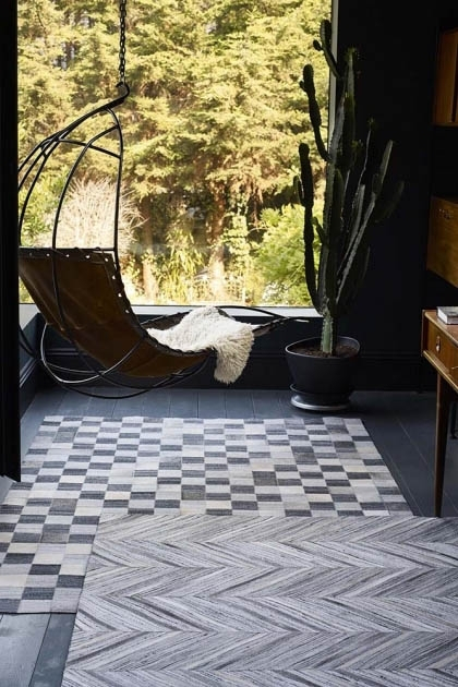 lifestyle image of Safari 03 Chevron Rug - 2 Sizes Available with hanging chair an layered on another rug with window background