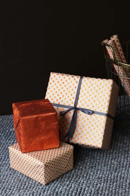 lifestyle image of Set Of 15 Sheets Of Hand Made Glitter Gift Wrap - Copper wrapped presents on grey rug and dark wall background