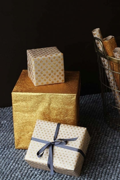 lifestyle image of Set Of 15 Sheets Of Hand Made Glitter Gift Wrap - Gold wrapped presents on grey rug and dark wall background