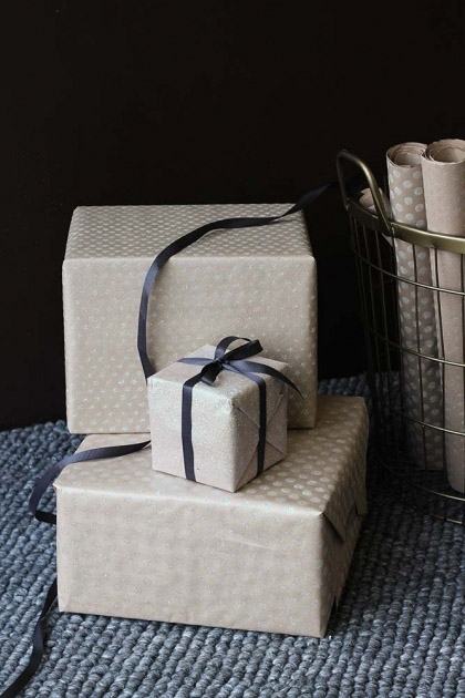 lifestyle image of Set Of 15 Sheets Of Hand Made Glitter Gift Wrap - White wrapped presents on grey rug and dark wall background
