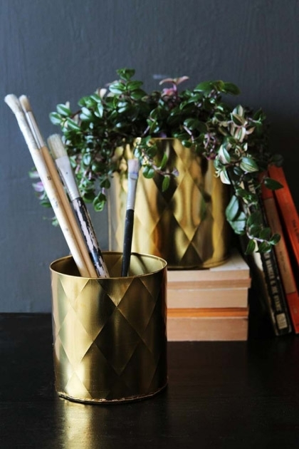 lifestyle image of Set Of 2 Gold Effect Faceted Planters  as pencil pot and plant pot on black table