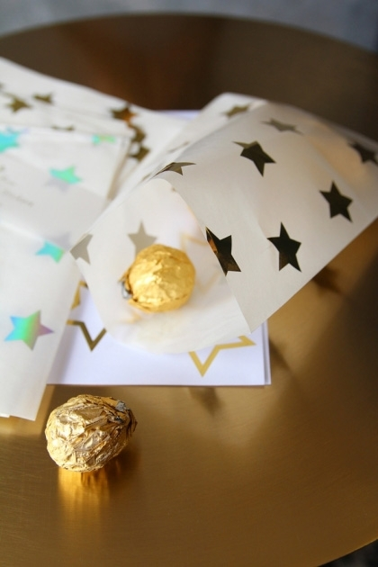 lifestyle image of Set Of 24 Foil Stars Treat Bags with gold chocolates inside and on gold table