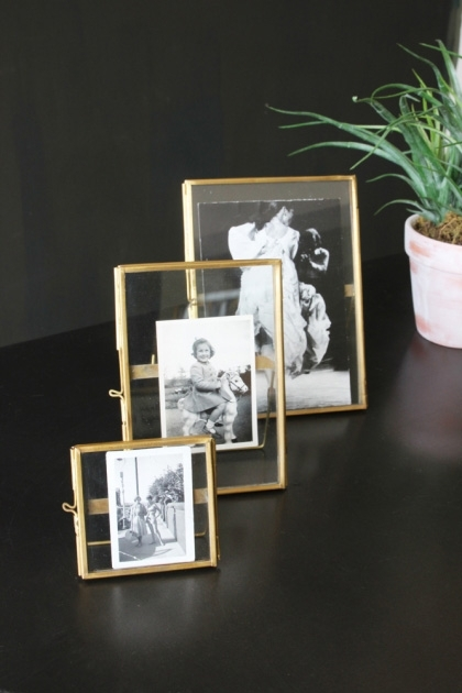 lifestyle image of Set Of 3 Brass Picture Frames in a row with black and white pictures in on black table with plant in background