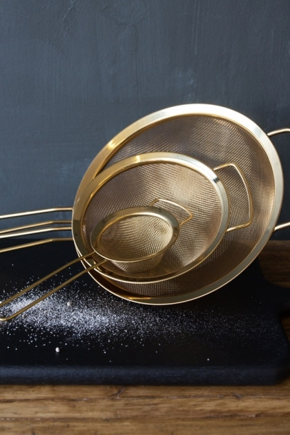 lifestyle image of Set Of 3 Gold Metal Sieves on black board and flour on wooden table and grey wall background