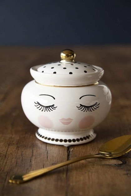 lifestyle image of Sleeping Face Sugar Pot & Lid with gold spoon in foreground on wooden table and dark wall background