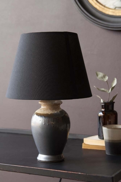 Lifestyle image of the Small Kiln-Fired Grey Table Lamp on black table with vase and round mirror on pale wall background
