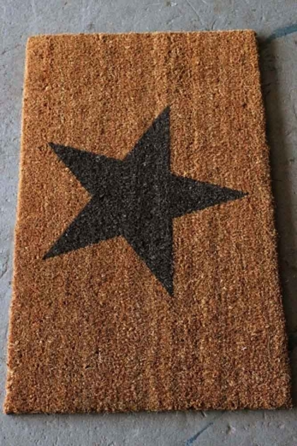 Brown traditional doormat with a charcoal black star in the middle on concrete floor lifestyle image