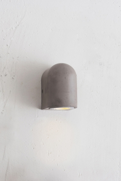 lifestyle image of Southbank Outdoor Concrete Down Wall Light lit up on white wall background