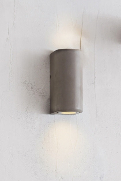 lifestyle image of Southbank Outdoor Concrete Up & Down Wall Light lit up on white wall background