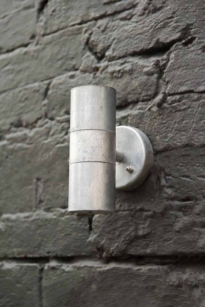 lifestyle image of St Ives Hot Dipped Up & Down Wall Light - Small on grey brick wall background