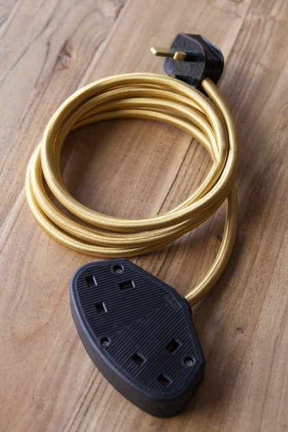 lifestyle Image of the Stylish 2m Extension Cable - Gold Lead With Black Sockets on pale wooden floor background