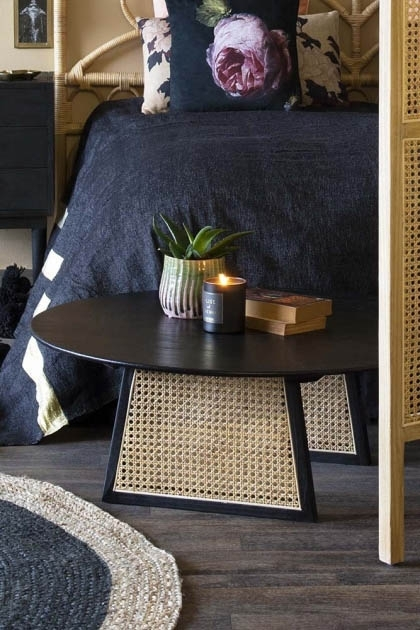Lifestyle image of the Sungkai Woven Cane Round Coffee Table in bedroom setting with bed in background and rug on wooden flooring