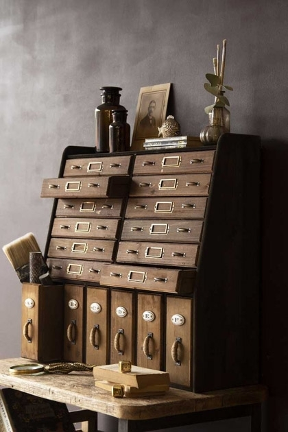 Lifestyle image of the Traditional Apothecary Cabinet Style Wooden Storage Wall Unit on distressed grey wall background and with ornaments on top