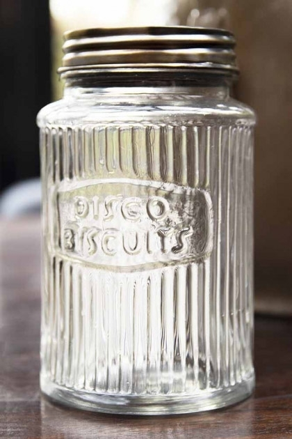 Lifestyle image of traditional clear ribbed glass storage jar with disco biscuits engraved on wooden surface